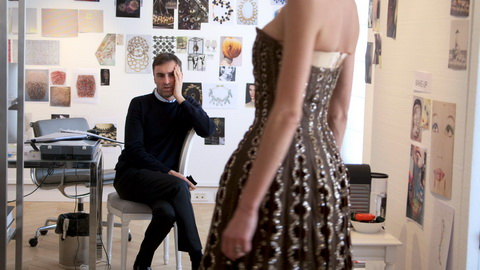 New Dior designer Raf Simons looks at a vintage Dior dress. Credit: CIM Productions